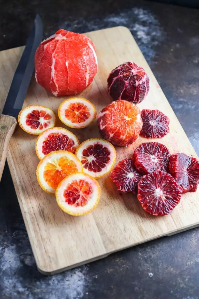 A pile of sliced blood oranges on a cutting board