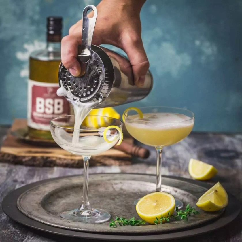 Pouring a cocktail through a strainer into a coupe glass