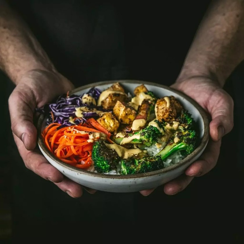 Two hands holding a bowl of tofu and veggies