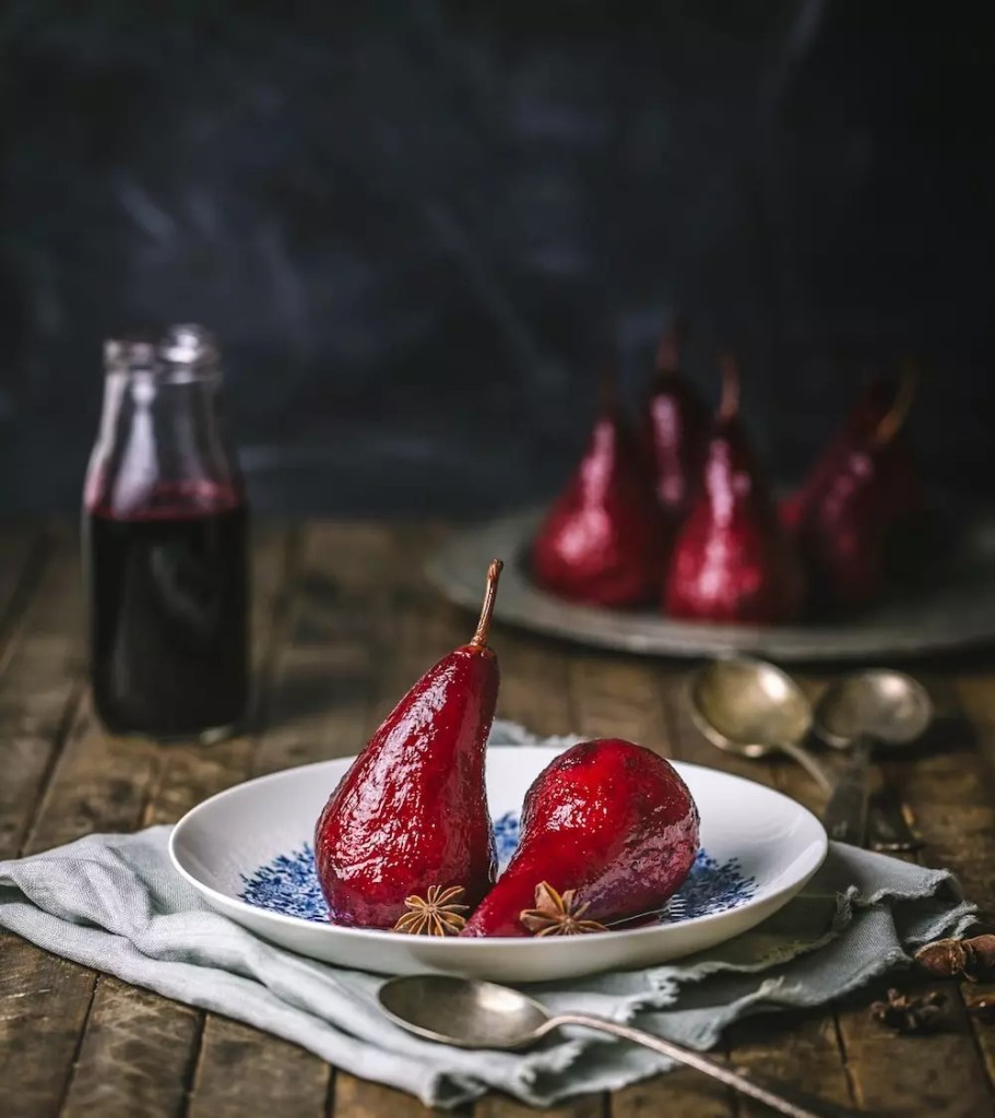 Red poached pears arranged on a plate