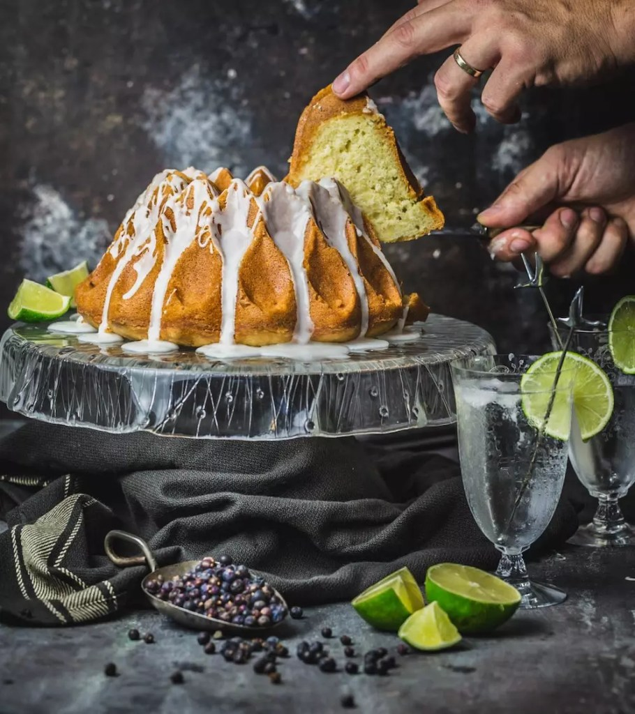 A slice of Bundt cake being lifted from the cake on a glass stand. Limes and junipers are arranged on the table