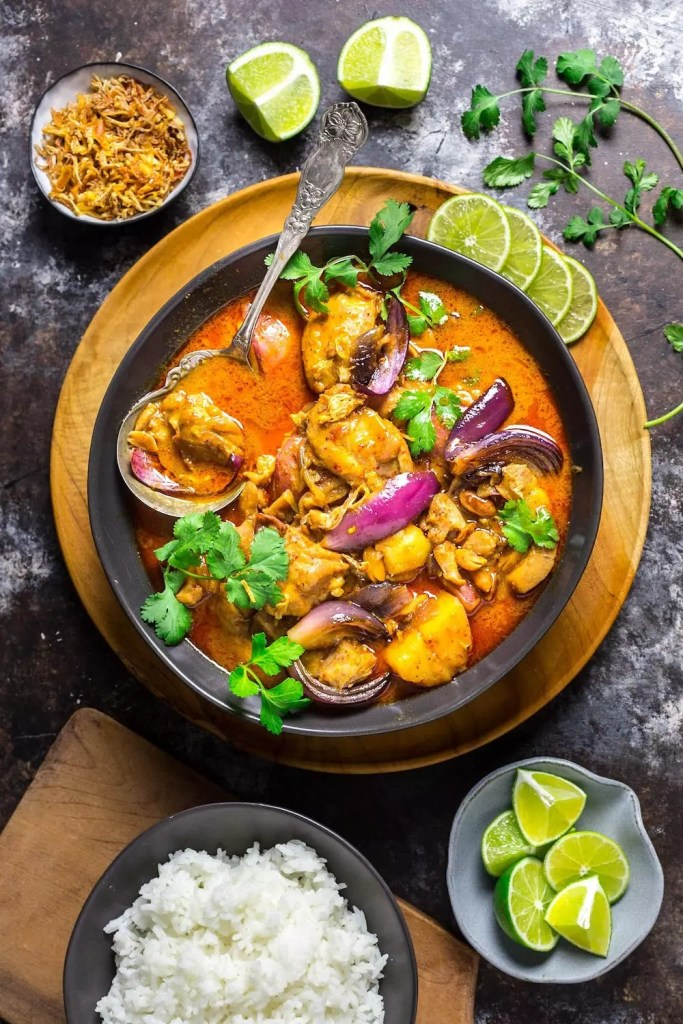 A bowl of colorful red curry with rice and limes around it