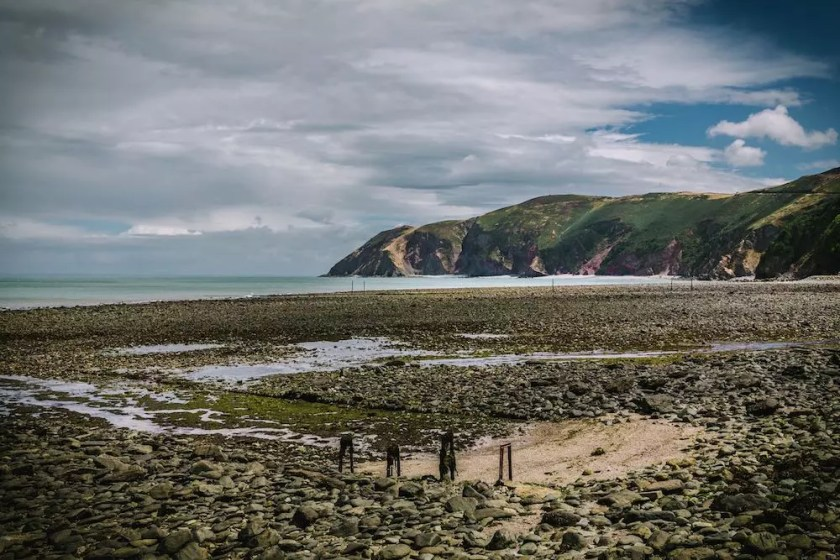 A rocky beach at low tide with cliffs in the background