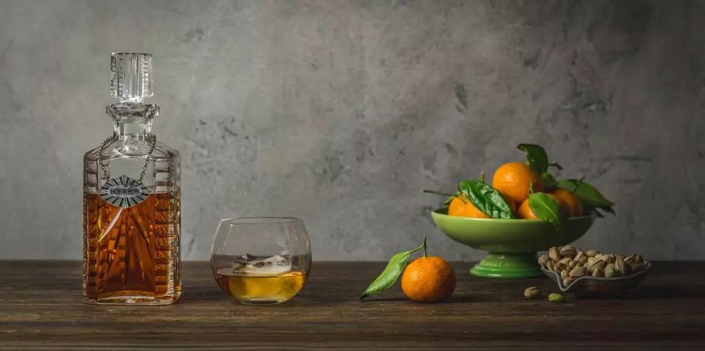 A decanter of whisky with a glass of whisky and a bowl of small tangerines