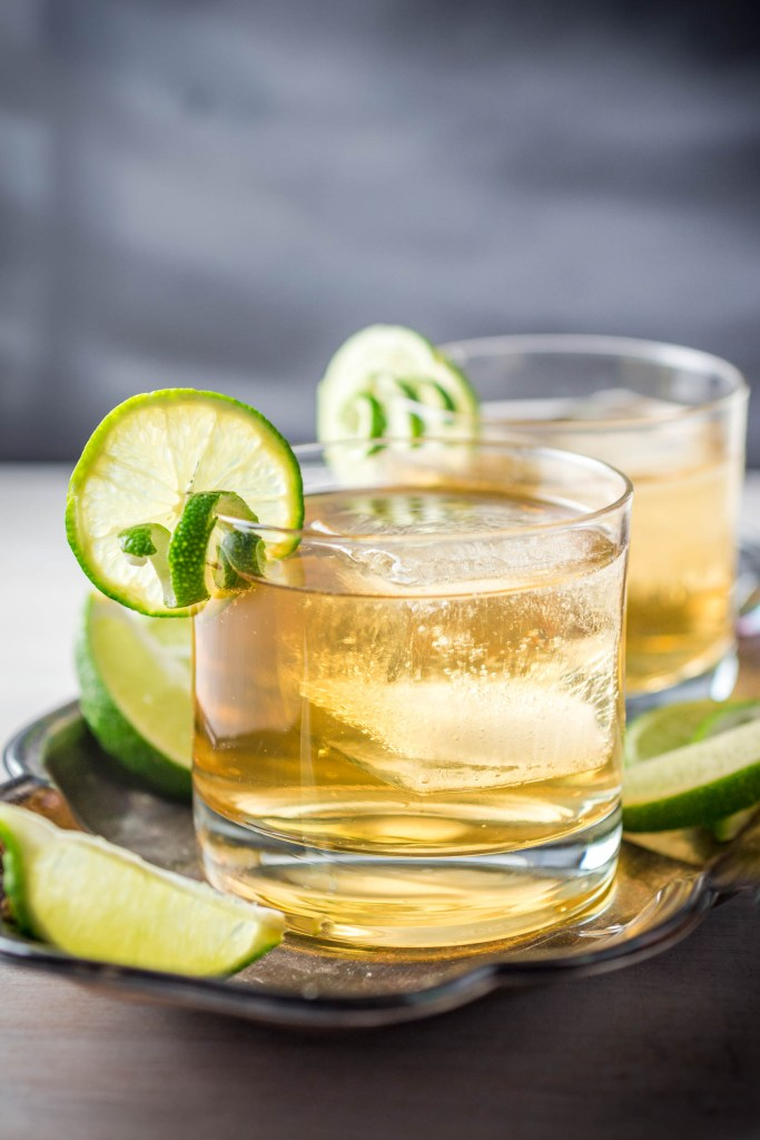 A close up of two cocktails with lime and ice