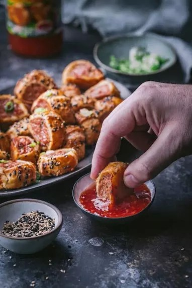 A hand dipping a sausage roll into some chili sauce