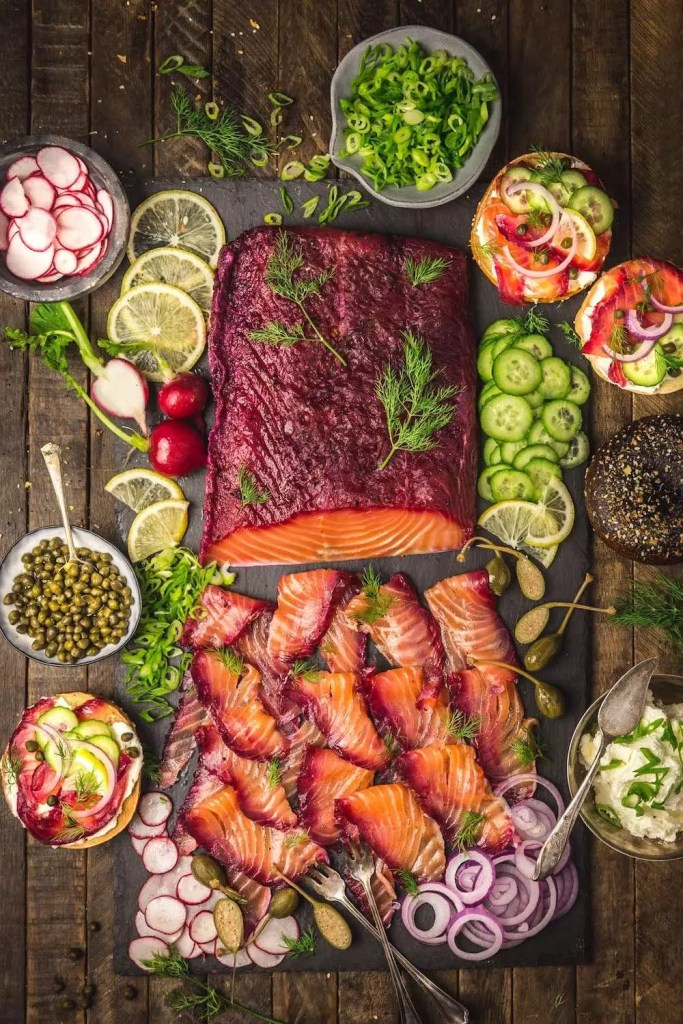 Cured salmon with a beet-red skin, sliced thin and surrounded by sliced veggies