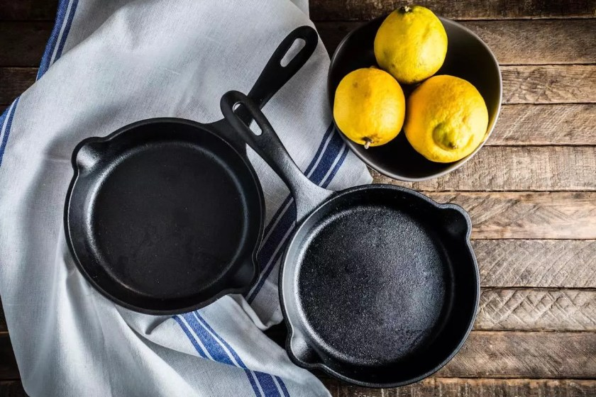 Two small cast iron skillets with a bowl of lemons