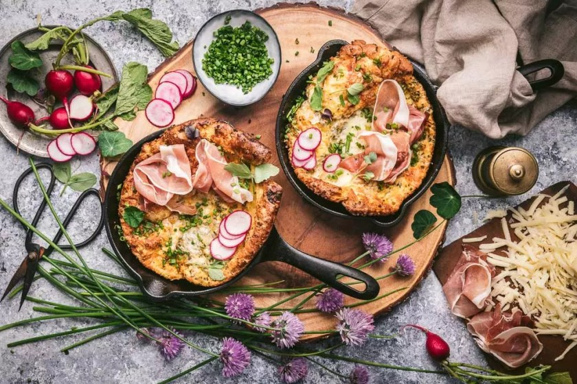 Two Dutch Babies in cast iron pans with radishes on top