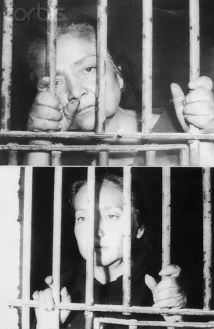 "ca. January 1964, León, Mexico --- Sisters Delfina Gonzalez Valenzuela, 52 (top) and Maria De Jesus Gonzalez, 39, (bottom) are shown behind bars at the San Francisco del Rincon jail. The sisters, along with another sister Eva and five other accomplices were indicted on homicide charges January 21, 1964 by a Mexican court in Leon. They were charged in the deaths of 11 persons whose bodies were found in a ""white slave"" concentration camp at a ranch near Leon, where a total of 17 women and 5 babies remains were found. The sisters owned two brothels and ran a sex slave ring that trafficked in young girls from 14 to 25. An estimated 2,000 girls passed through the ring, lured with promises of jobs as maids for upper class families. The sisters were convicted of first degree murder, slavery and other crimes and sentenced to the maximum penalty of 40 years in prison. --- Image by © Bettmann/Corbis"