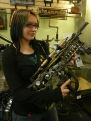 Amanda Tucker displays a steampunk rifle (photo by Tim Hacker)