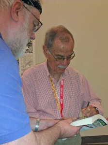 Stan Goldberg signs a book for a fan.