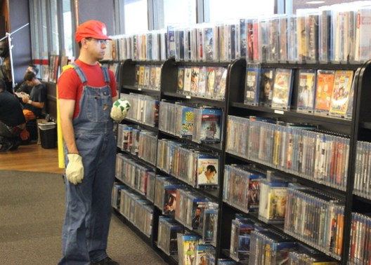 Mario peruses the blu-ray section for a re-release of Super Mario Bros. the movie.