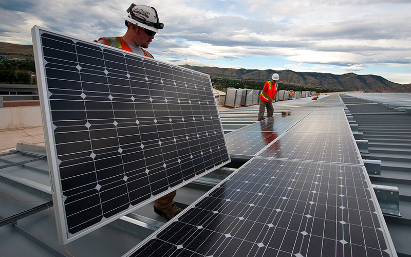 "Workers install photovoltaic panels on roof in this file photo. A new report says Phoenix gained solar capacity in the past year, but was outpaced by cities in other states that saw aggressive growth. (<a href=""https://flic.kr/p/fozyTg"" target=""_blank"">Photo</a> by Dennis Schoeder/<a href=""https://www.flickr.com/photos/departmentofenergy/"" target=""_blank"">Department of Energy</a>)"