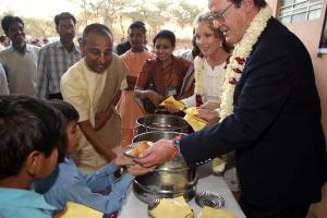 On 17 November, 2005, UNICEF Goodwill Ambassador Sir Roger Moore helps serve food to local children, at the Akshaya Patra Foundation in Jaipur, capital of the north-western state of Rajasthan. He is assisted by Akshaya Patra Foundation Vice Chairman Chanchalapati Dasa (centre) and Lady Kristina Moore (second from right). The Government-supported NGO currently feeds close to 273,000 impoverished schoolchildren nationwide through its mid-day meal programme. From 14 to 19 November 2005, UNICEF Goodwill Ambassador Sir Roger Moore and his wife Lady Kristina Moore visited India to promote the use of iodized salt and to raise awareness of iodine deficiency disorders (IDD). Half of the 26 million children born in the country each year are at risk of iodine deficiency disorders such as brain damage, speech and hearing defects, delayed motor development and impaired physical growth, and significant loss in learning ability. During their stay, Sir Roger and Lady Kristina visited New Delhi, the capital, and the states of Rajasthan and Maharashtra, where they met with government and local authorities, salt producers, representatives from civil society, the media and UN agencies, as well as with members of Mumbai's feature film industry. They also toured schools and other UNICEF-supported community projects and sites.