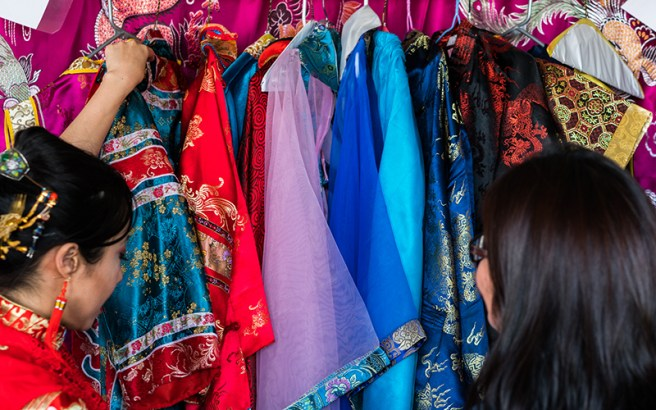 Volunteer Amy Oho (left) shows Chinese imperial costumes that present a colorful showcase of the diverse Chinese culture. (Photo by Daria Kadovik/Cronkite News)