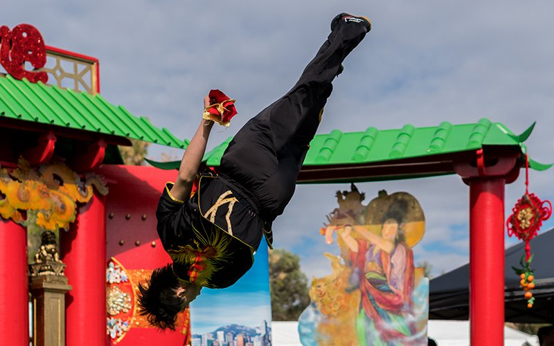 A student from Phoenix Wushu Academy performs an aerial maneuver during a Wushu performance. Wushu is a martial art that pushes the utmost limit of the human body, challenging one to do aerials, butterfly twists, jump kicks all several feet above the ground, according to Phoenix Wushu Academy. (Photo by Daria Kadovik/Cronkite News)