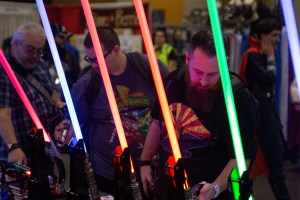 """Jake Talbert browses prop lightsabers from the """"Star Wars"""" movies during Phoenix Comic Fest. Lightsabers are allowed under the new security policy. (Photo by Nick Serpa/Cronkite News)"""