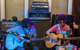 """Band members of Fear and Love Rob Dinuto, left, and Kevrie Howard run through their song """"Business As Usual"""" before recording an acoustic session for Arizona Music Podcast. (Photo by Nicole Gimpl/Cronkite News)"""