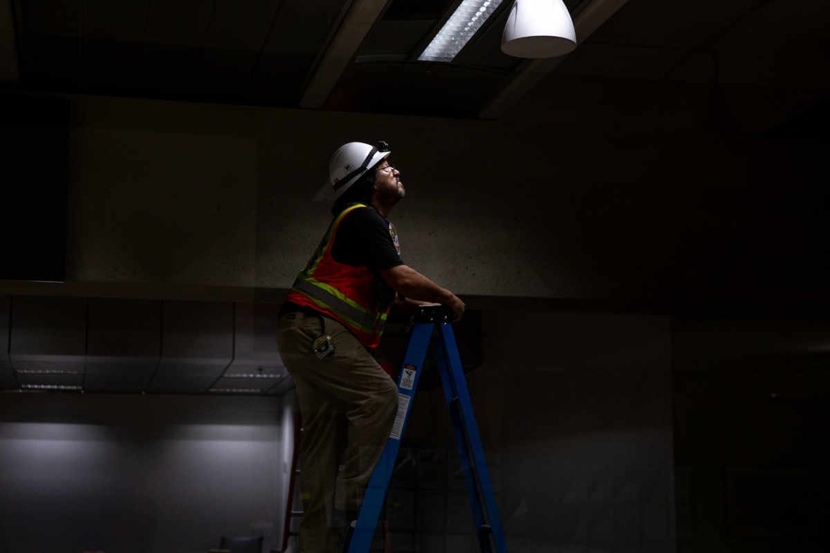 A worker fixes a light in the College Depot at Burton Barr Central Library. Renovations are still under way, but spokeswoman Lee Franklin said the library will be open for business June 16.(Photo by Ellen O'Brien/Cronkite News)