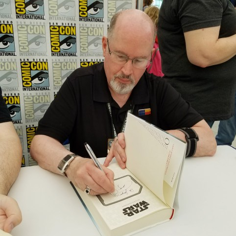 Timothy Zahn autographing books for fans.