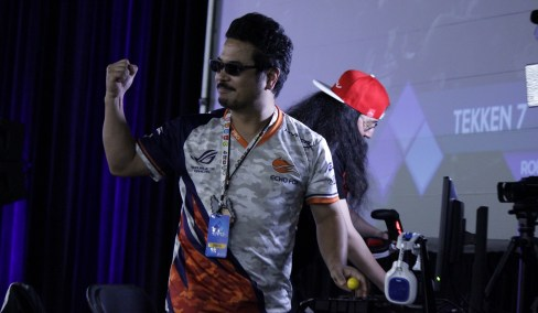 Tekken director Katsuhiro Harada raises a triumphant fist after winning a match against another player nicknamed Scarlet.