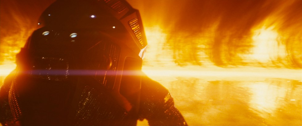 A person stands in a heavy space suit designed to withstand the force of the Sun with a blistering, blinding light tearing into frame in front of them