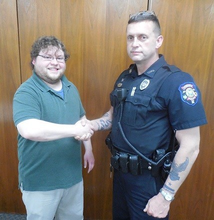 Head Corinth Librarian Cody Daniel shakes hands with Officer Clifford Nix.