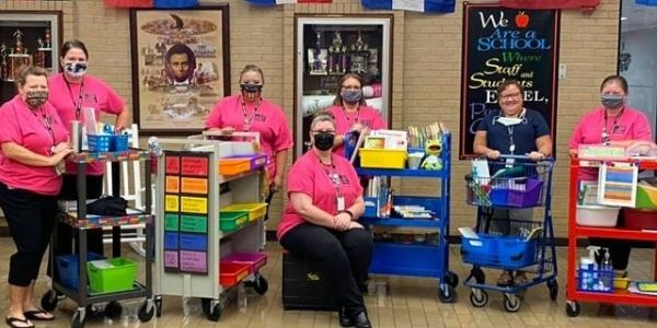 Staff members pose with carts filled with supplies.
