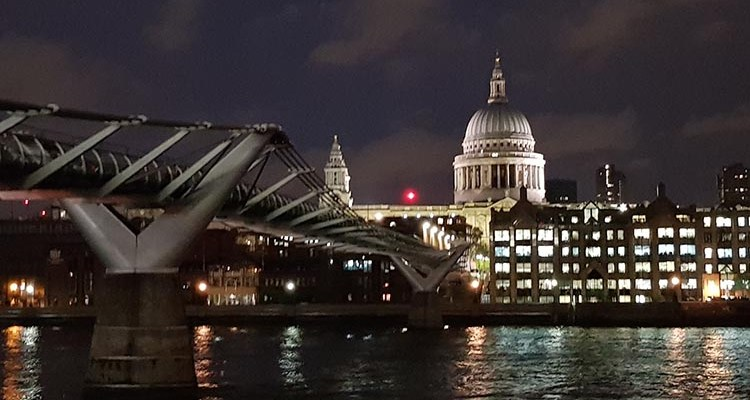 Night time photo of the millennium bridge across the river thames to St Paul's Cathedral.