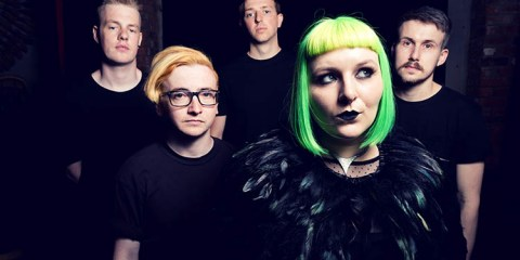 Promo photo of the band Wynona Bleach, female singer with green hair standing at the front, with 4 males behind her