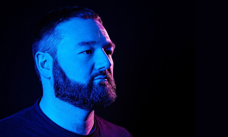 Maddox Jones side view under blue and red lights with a black background