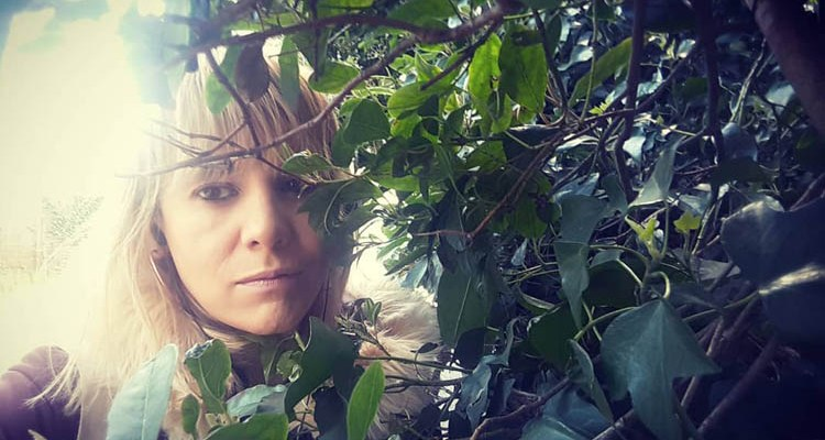 A photo of singer, Keeley, in some shrubbery
