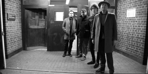 Black and white photo of the band Cronin, standing outside the entrance to Highgate Underground Station in London