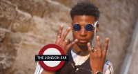 SAM O.G. wearing sunglasses giving the peace sign in front of The London Ear roundel