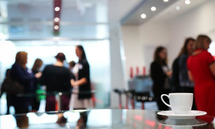 A Coffee cup on a table at a meeting with participants out of focus in the background - Why You Shouldn't Kill Your Online Meetings - nessymon
