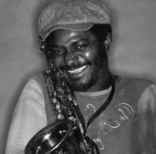 Pee Wee Ellis hugging his saxophone. A black and white photo. Image from https://secondhandsongs.com/artist/12536