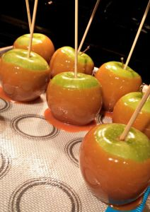 Apples dipped in caramel cooling on a nonstick surface