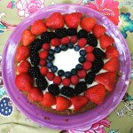 Photo of a cheesecake decorated with strawberries, blackberries, raspberries and blueberries on a pink plate.