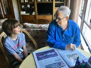 Un abuelo haciend o crucigramas del periódico con su nieto