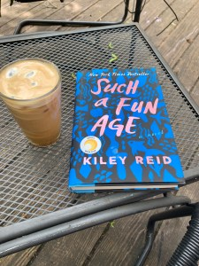 A book title Such a Fun Age and a coffee glass on a patio table.
