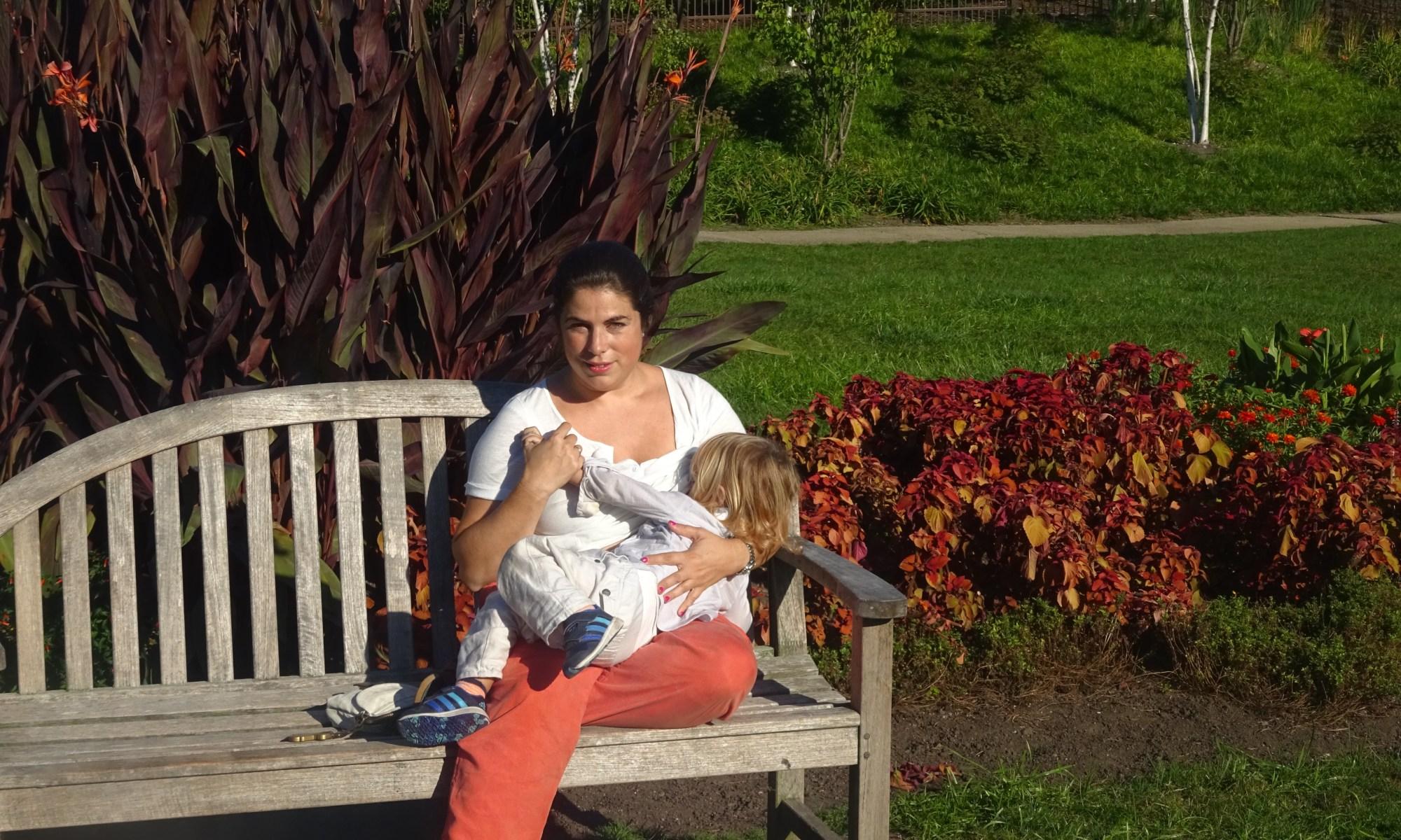 Amother sitting ona bench breastfeeding her child