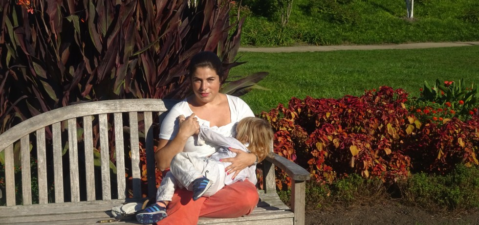 Amother sitting ona bench breastfeeding her child