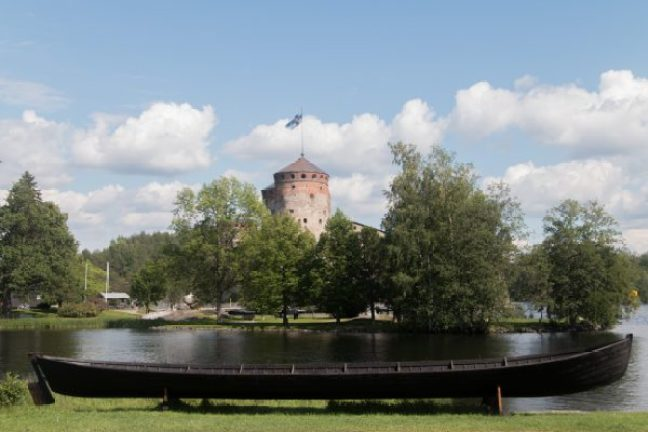 14:47 Castle of Savonlinna in the background and a traditional 'Church Boat' in the foreground.