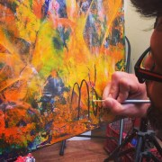 Abstract painter L.A. Artist Nestor Toro signing a finished painting