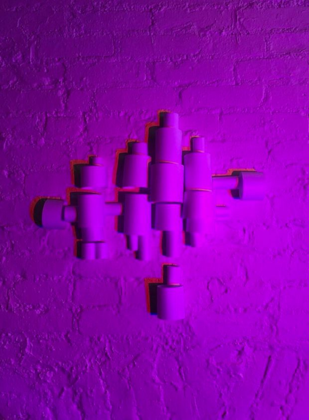 an image of the paper sculpture with a purple light source projected onto the piece