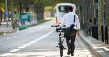 businessman-walking-with-bike-in-street-after-work_1262-5982
