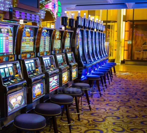 Row of one armed bandit slot machines in casino brightly lit