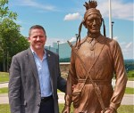 Mohegan Tribal Chairman Kevin Brown stands with a bronze sculpture of his ancestor Mohegan Chief Matahga, Burrill Fielding. (Mohegan Sun)