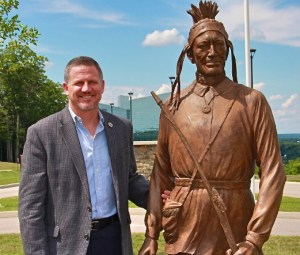 Mohegan Tribal Chairman Kevin Brown stands with a bronze sculpture of his ancestor Mohegan Chief Matahga, Burrill Fielding. (Mohegan Sun) Read more at http://indiancountrytodaymedianetwork.com/2014/09/15/cheeseburgers-wood-pellets-paradise-mohegan-diversification-goes-fat-frying-pan-156184